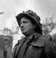 Pte. Gus McKinnon of the Highland Light Infantry of Canada advancing toward Caen, France, 9 July 1944.