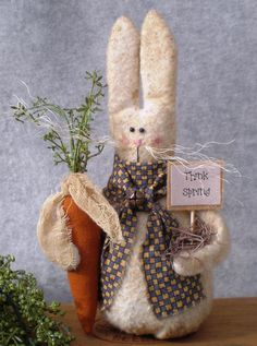 "Cute 8"" Think Spring Bunny made from warm and natural that has been coffee stained for an aged look. Bead eyes, embroidered nose and mouth, and sisal rope whiskers. Coffee-stained carrot with plastic green leaves and a coffee stained scrim tie is tucked in one arm, and a Think Spring sign in a nest of excelsior is in the other arm. A cute homespun scarf is wrapped around his neck and knotted with a brown bell accent. The bunny is stuffed with poly fiberfill and is weighted with sand."