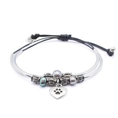 A 2 strand, adjustable braided leather bracelet adorned with silverplate crescents, freshwater pearls and silverplate beads. Handmade in the USA.