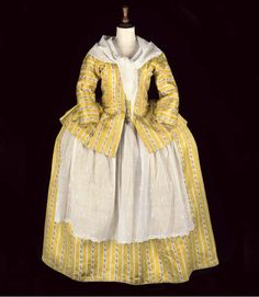 A LADIES' ENSEMBLE OF YELLOW STRIPED SILK, 18th CENTURY  comprising round skirt and full skirted open-front jacket with integral waistcoat panels, the yellow silk woven with a pink-sprigged white stripe; together with a whitework apron panel and muslin kerchief