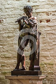 Sculpture of young man playing the flute in Branitz palace. Germany. Europe.