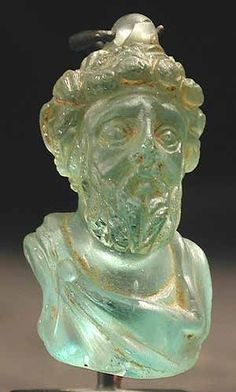 "Glass portrait head of the Emperor Septimius Severus. Jerusalem, c 193 CE to 211 CE. Dimensions: 1.375"" (3.5cm) high x 0.75"" (1.9cm) wide."
