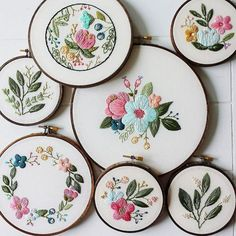 Hand embroidery, displayed in same-finish wooden hoops. Reminds me of a collection of ceramic plates to be hung on the wall or a montage of art / photo prints, all in same-finish frames to bring the whole display together..