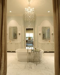 Amazing master bathroom with pale blue walls paint color, marble tiles floor, freestanding tub, polished nickel floor-mount bath filler, polished nickel directoire table, white single bathroom vanities with marble countertops and wall-mount faucets.