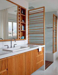 Este banheiro tem iluminação de camarim no armário com espelho. O boxe é fechado por painel ripado, que funciona como porta-toalhas. Reforma do arquiteto Felipe Rio Branco