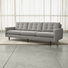Petrie is a grandly scaled three-seat sofa that sits at the intersection of mid-century and today, with clean lines and tailored cushions expertly button-tufted by hand.  Now a Crate and Barrel classic, its pure 1960s aesthetic is scaled deep so you can sit firm and upright, but also slouch back in comfort.  Well-suited to make a great impression, the menswear-inspired fabric tailors Petrie's sleek, boxy cushions and slim track arms with heathered color and soft texture.