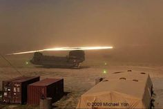 Sand hitting the rotors creating luminous halos above a Boeing CH-47 Chinook