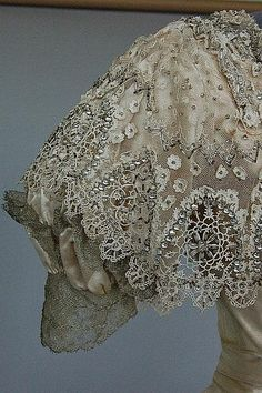 A Jeanne Hallée (1880-1914) ball or presentation gown, 1903, with woven label as part of the waistband, '3 Rue Ville L'Eveque, Paris', the bodice with deep point to waist, square neckline adorned with reticella style chemical lace, studded with rhinestones and bugle beads, silver lace trim, the trained skirt with elaborate skirt front and zig zag bands of silver lace to the hem,