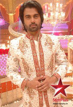 Krishna looks like a prince in the red and white jodhpuri.