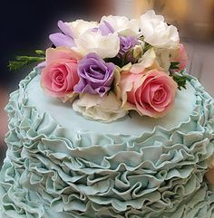 Pale green ruffle wedding cake with fresh Flowers to match brides bouquet.   https://www.thecakelabbakery.com/