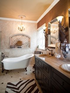 Designer Bathrooms Fit for Royalty: The clawfoot bathtub makes a striking statement directly below a decorative marble niche and embellished gold chandelier. The travertine-topped double vanity and grass cloth walls deliver a unique finesse, creating the ultimate bathroom retreat.