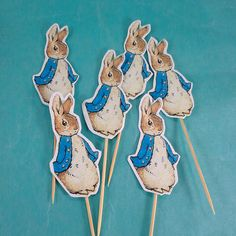 Peter Rabbit cup cake cake toppers or party pics. Six Peter Rabbit picks on a 2 1/2 stick. Each topper is about 3 1/8 tall - not including the stick. Perfect for shower or birthday decoration. This listing is for six single sided cup cake toppers - the stick is visible on the back. (Contact me if youd prefer a double-sided option where the same image would be on both sides and the stick is not visible.) READY TO SHIP I ship first class. Expedited shipping is available upon request...
