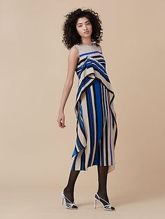 Mixed prints, an asymmetric ruffle and front slit add movement to this modern maxi dress.