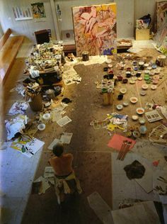 Willem de Kooning in his studio, with a bottle of safflower oil and bowls of paint on his worktable, 1971.