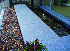 Complement your water feature with Silver Grey Granite Paving like this garden by Ben McKee Landscapes (also shown are our Scottish Beach Pebbles)