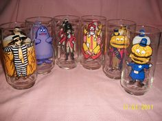 Six vintage McDonalds drinking glasses from the 1970s. There is Captain Crook, Grimace, Hamburglar, Mayor McCheese, Big Mac, and