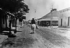 Lone horseman riding through Tucson, Arizona, 1880.