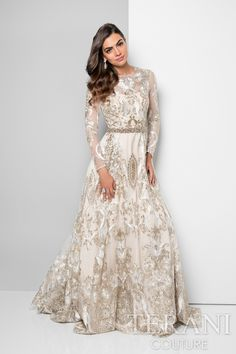 Designer dress with two-tone metallic embroidery that isartfully placed on this red carpet ready long sleeve ball gown. This dream dress is finished with a matching beaded waistline that sets off the look and comes in white gold and blush gold.