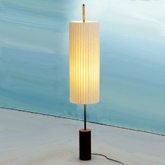 A column-like cylindrical lamp featuring an elongated, natural cotton ribbon shade.