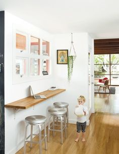Small space solution for an eat-in kitchen: wall-mounted oak bar with bar seating. A window between the rooms helps the space from feeling boxed in.