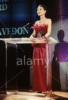 """The actress and UNICEF Special Ambassador Audrey Hepburn photographed presenting an award for the fashion photographer Richard Avedon in the ceremony of the """"1988, Council of Fashion Designers of America Awards"""", held at the Metropolitan Museum of Art in New York City, New York (USA), on January 09, 1989.Audrey was wearing:Evening gown: Givenchy (strapless, of satin in the beautiful scarlet shade, bodice decorated with feathers in scarlet and black, at the waist a precious embroidery with…"""