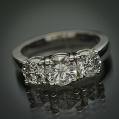 Big wow factor with this classic 14K white gold engagement ring. The 3 round brilliant diamonds weigh 1.76 carats in total, are very bright and face up great to the naked eye. The diamonds are HI in color with I2 imperfections. Ring size 6 Can be sized as well.