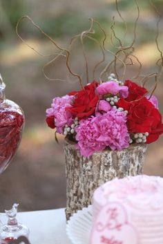 Pink Peonies, Red Roses, Silver Brunia Berries and Curly Willow in a faux Tree Trunk