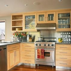 The dishwasher is conveniently located next to the sink for easy loading. Glass-front kitchen cabinets near the oven allow cooks to take inventory at a glance. Open shelves accentuate horizontal lines and provide access to items via the kitchen or dining room./