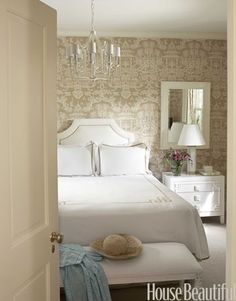 wall papered guest bedroom with white linens