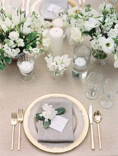 elegant table scape in gold, grey and white with pillar candles and tea lights