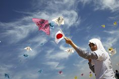 Palestinian children fly kites bearing Palestinian and Japanese flags to show solidarity with Japan in the Gaza strip on the third anniversary of the March 11 earthquake and tsunami in Japan.