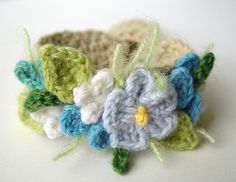 Made on a tan cotton base, cashmere flowers and leaves (with some sprigs of celery green mohair) in the colors of light blue, sky blue, turquoise, white, and 2 shades of green. Has a self loop and toggle for closure.