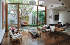 O terreno tinha uma jabuticabeira que orientou o projeto. Assinado pelo arquiteto Jorge Siemsen, ele ganhou formas orgânicas para envolver a árvore. Uma das paredes é de vidro, que proporciona a visualização do jardim em todos os ambientes