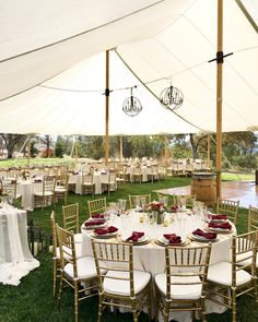 Wedding reception under a sailcloth tent | Metal orb chandeliers + wine barrel cocktail tables + wooden dance floor + lots of gold and red | Celebrations! Party Rentals and Tents | Catering and coordination by Farm To Table Catering