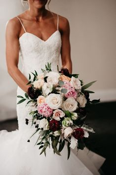 The Bride's bouquet of ivory flowers and greenery with pops of blush and deep maroon. Photo by Erin Northcutt and Feather + North, Wedding Planning by Bella Baxter Events. Floral by Ena Fowler Floral Design.