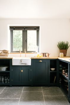 A farmhouse sinks, brass taps and dark blue Shaker cupboards in deVOL's Leicestershire Kitchen in the woods