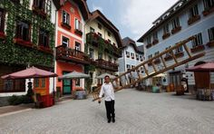 CHINA'S KNOCK-OFF LANDMARKS:  A construction worker walks with a ladder in the replica village of Austria's UNESCO heritage site, ... - REUTERS/Tyrone Siu