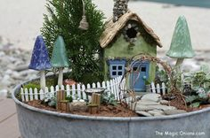 Love this fairy garden with white picket fence and pretty toadstools and fairy house - More enchanting photos of this magical FAIRY GARDEN on The Magic Onions Blog and FairyGardens.com