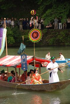 Mifune Matsuri. A woman dressed in junihitoe riding a flat bottomed boat along with others.