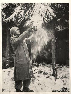 1945- U.S. 101ST AIRBORNE DIVISION SOLDIER FILLS HIS CANTEEN CUP WITH SNOW FOR MAKING COFFEE IN BELGIUM FOREST NEAR FOY.