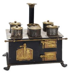 German tinplate stove with claw feet, has three brass oven doors and latches, four burners and water heater, fitted tin pots with brass lids, chimney with brass cap, and brass towel bar. Probably Bing, circa 1900.