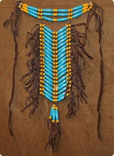 """The breast plate is 22"""" by 18"""" in length and is made out of plastic beads and brown leather strips."""