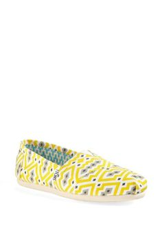 Bright yellow Toms with a signature Jonathan Adler print