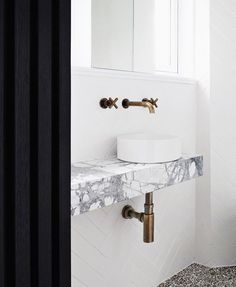 Black and white bathroom with marble ledge instead of counter and small floating sink.