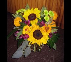 The gold and purple hues of earlier sunsets marking the end of summer and beginning of autumn are captured in this arrangement of sunflowers, purple alstromeria, luecadendron, seeded eucalyptus, salal, green buttons and seasonal marigolds and zinnias locally grown by Flower Hill Farm of Beaufort, MO.