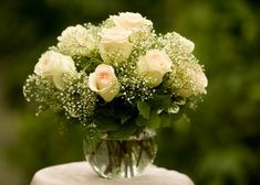 """baby's breath and roses in """"fish bowl"""" style vase"""