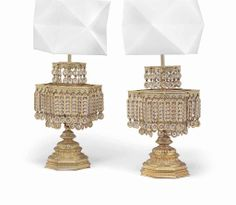 A pair of gilt-metal and glass table lamps late 20th century. The reeded central shaft supporting two hexagonal tiers mounted with glass drops, with later white canvas shades #lestroisgarcons
