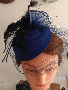 Hola, ofrecemos un elegante bibi azul oscuro, hacer un base molde azul oscuro, un velo, una cinta azul terminado, una pequeña perlettes azul montado sobre tallos y plumas negras.