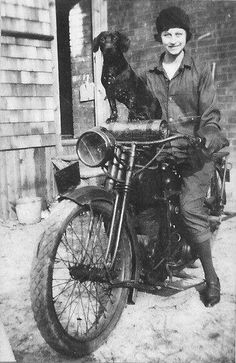 A girl and her dachshund on a motorcycle, circa 1918.