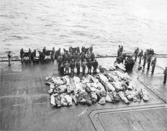 Preparation for the traditional burial at sea for those killed on the USS Saratoga by Japanese kamikazes during the Battle of Iwo Jima, Feb 1945